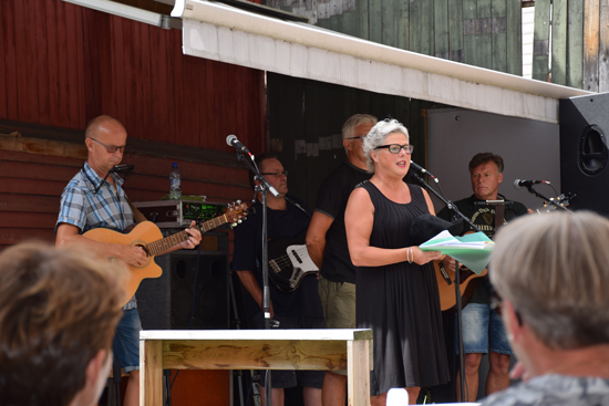 Lørdag 9. august. Ellen Nordby i Tante Gerdas Scene ønsker velkommen til en fullsatt bakgård.